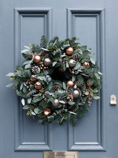 Handmade exclusively for Cox & Cox by luxury artisan florist Flowers By Passion, our Christmas wreaths are crafted using a sumptuous array of seasonal foliage, beautiful copper and grey baubles, frosted pine cones and miniature copper bells. The perfect centrepiece for your front door, each unique wreath has been made on a mossed ring frame and includes a mix of preserved eucalyptus in green-blue tones, scented blue pine that evokes the scent of Christmas, pine cones and shatterproof…