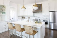 Hudson Valley Lighting Lambert Pendants hang over a white island topped with a white quartz waterfall countertop seating three gold suede barstools and fitted with a farmhouse sink with a Delta Champagne Bronze Trinsic Pull-Down Kitchen Faucet.