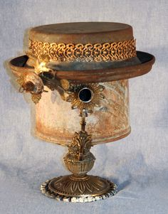 Hand-crafted birdhouse made from an old fuel can with the top of a milk can for a hat. Ribbon on the hat constructed from an old decorative tissue box cover with other bits and pieces.