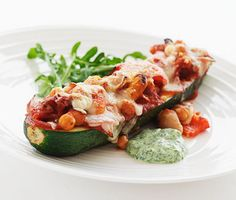 Denna ugnsrostade zucchini med godsaker har en fenomenal smak. Zucchinin fylls med bland annat kikärter, vita bönor, krossade tomater och smakrik parmesanost före den rostas i ugnen. Servera med en crème av mixad rucola, minifraiche och honung.