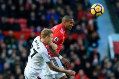 Manchester United's English midfielder Ashley Young beats Burnley's Scottishborn Canadian midfielder Scott Arfield in the air during the English...