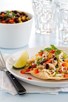 Baked Chicken Tostadas are super easy to make, and full of the good stuff. Fire roasted corn, slow cooker shredded chicken, black beans, salsa and plenty of flavor make this a weeknight dinner you'll put on regular rotation.