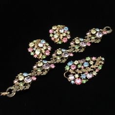 Very pretty multi-colored rhinestones set comprised of bracelet, pin and earrings. At first glance, these look like a set by Hollycraft, but in fact this is a Lisner design. All pieces are hallmarked