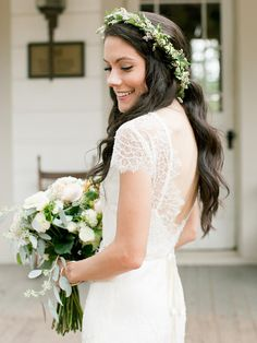 The perfect accessory for a half-up wavy bridal hairstyle? A simple flower crown of greenery and small white blooms.