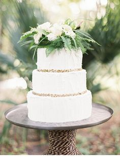 pretty white wedding cake with simple florals and greens