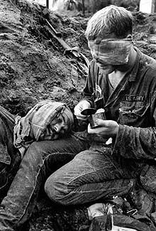 HENRI HUET Vietnam, 1966  Wearing a bloody bandage over the left side of his face, medic Thomas Cole of Richmond, Va., cradles the head of Staff Sgt.Harrison C.D. Pell from Hazelton, Pa., of the First Cavalry Divison. (AP)