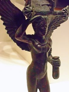 Bronze handle from a ritual patera in the shape of a Lasa divine attendant of Turan the Etruscan goddess of Love holding a perfume flask 350-300 BCE. The Getty Villa in Malibu, California.