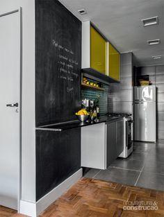 Referência de Piso. Pisos diferentes delimitam a fronteira entre os ambientes. Na sala, há tacos de perobado-campo finalizados com resina (Bona). Na cozinha, porcelanato cinza (60 x 60 cm, da Portobello). Parede com tinta esmalte sintética fosca de quadro-negro (Coralit, da Coral).