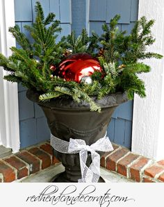Budget Christmas Decorating Idea: Use your gazing ball in and urn with left over tree trimmings.