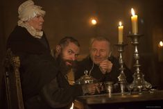 Les Mis (2012) | A gaunt Hugh Jackman (Valjean), Heather Chasen (Mme. Magliore, the Bishop's housekeeper) and the original stage production's Valjean, Colm Wilkinson (Bishop of Digne), in Les Misérables.
