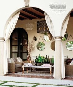 curtains, arches, recycled bottles & mirrors....inviting patio area.