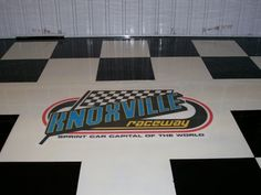 Checker Epoxy Floor With Graphic - Des Moines, Iowa Area - Decorative Concrete Kingdom.   Repin & Click For More Info or Quote @ Your Home / Business.