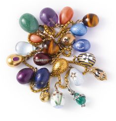 TWENTY-ONE MINIATURE EASTER EGG PENDANTS, CIRCA 1900 Comprising a carved amethyst and gold egg and a carved tiger's eye egg, both probably Fabergé; a small aventurine quartz egg; a gold and pale blue hardstone egg; a gold egg set with faceted pink tourmaline; a gold egg enameled transparent purple, Fabergé. ( Other's by various makers )