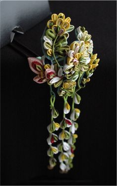 Kanzashi flowers in what looks to be thin crepe sewn to green-wrapped stems ~ artisan level!