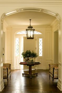 The paneled entry hall features an oversized front door with leaded glass sidelights and traditionally detailed arched transom. Herringbone walnut flooring helps to unite two strong cross axes of the space. Entry Stairs, Entrance Foyer, Entry Hallway, Entryway, Grand Entrance, Foyer Staircase, Grand Foyer, Staircases, Harrison Design