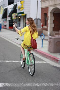 Thumbs UP! traveling in yellow dress on vintage bike.