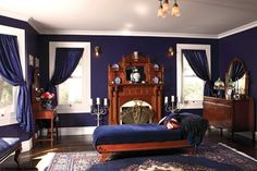 The midnight-blue master bedroom is the perfect setting for the 1920s Egyptian Revival chaise lounge. The mantel, which was bought on eBay and came from Philadelphia, is in the Eastlake style.
