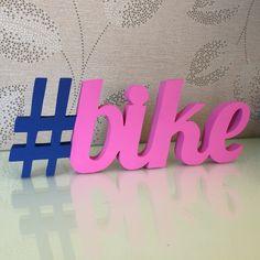 #bike Hashtag decorativa    Mais uma peça ideal para decoração da sua casa ou festa, sendo também uma ótima opção para presentear com com muita exclusividade, estilo e criatividade.    Peça em MDF de 15mm medindo 8cm de altura por 23cm de comprimento.  Tem pintura artesanal e acabamento fosco.  F...