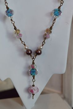 This necklace has beautiful blue & pink lamp work beads, clear & smoky glass beads and glass pearls that are wire wrapped with bronze wire. 21 1/2 inches.