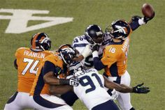 Denver Broncos' Peyton Manning is hit by Seattle Seahawks' Cliff Avril (56) during the first half of the NFL Super Bowl XLVIII football game Sunday, Feb. 2, 2014, in East Rutherford, N.J. Manning was charged with an interception on the play. (AP Photo/Charlie Riedel)