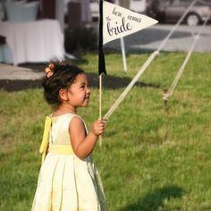 Flower girl carries a pennant/flag?