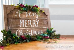 Inviting Christmas decor is easily achievable with a blank wood pallet, antiquing wax, hand lettering and Christmas picks!