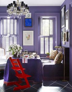 The velvet-covered banquette serves as plush seating at the dining table, draped in purple burlap from Elegant Fabrics. Designer David Kaihois' three-year-old daughter sits in the red Tripp Trapp high chair by Stokke.