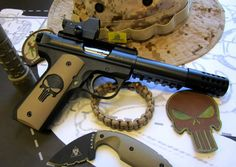 Ruger's 22/45 ..22 caliber semi-auto light weight pistol with compensator, holographic sight, and Punisher grips.