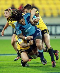 Tackling is just aggressive hugging. A couple of Hurricanes take on Ma'a Nonu.
