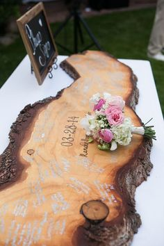 Instead of a regular guestbook, have your guests sign a polished plank of wood for a rustic touch.     Photo via  Deer Pearl Flowers .