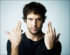 "ok...don't  know  much  about  Dane  Cook  ...so someone please tell me WTF this hand thing is he's doing?!?!  Is it like a fight or flight version of someone giving the bird, ""I wanna flip you off but I'm afraid you will yell at me so I'm gonna just put up two fingers to confuse you though I fully know I'm giving you the bird"".  He's just weird...."