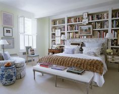 bed in front of bookshelves, love the wall lamps attached to bookshelves to save floor space and keep access to more books.