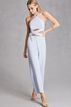 A woven jumpsuit by Selfie Leslie™ featuring a high neckline, cami straps, a crisscross cutout design at the front waist, a wide cropped leg, mock back welt pockets, and an exposed back zipper.