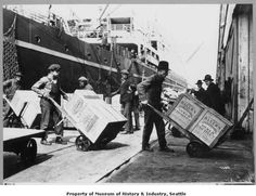 This 1906 photo by Asahel Curtis shows a group of longshoremen moving crates of shredded coconut from a ship to a transit shed at the Seattle waterfront. Large cranes lifted the crates from the ship's hold in heavy cargo nets and lowered them to the dock. The crates of coconut would stay in the transit shed until they were shipped by rail to their final markets