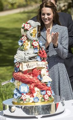 Kate inspects a cake that was specially designed to celebrate the opening of Hampton Court Palace's newly-unveiled Magic Garden