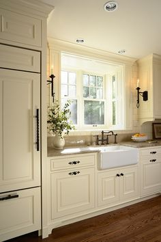 Lovely kitchen cabinets and farmer sink, the covered frig door and the black wrought iron hardware.