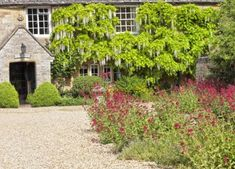 Traditional English cottage courtyard with gravel driveway, stone mushroom, colourful garden flower. Charming stone house is surrounded by white wisteria Driveway Repair, Gravel Driveway, White Wisteria, Stone Houses, Colorful Garden, Garden Supplies, Castle, Cottage, Traditional