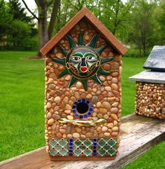 "Perfect gift for Father's Day. Tall cedar birdhouse with stones and river rock collected from the shores of Lake Michigan, local rivers and from creek beds. Also embellished with Aztec Sun, Mexican hand painted tiles and mini blue glazed tiles.Brass handle for perch. T Suitable for outdoor or indoor décor.   15 1/2"" high X 8 1/2"" wide X 9 1/4"" deep       1 1/8"" opening"