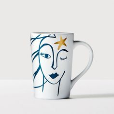 A white mug with a blue sketch design of a star-crowned Siren. Available exclusively online.