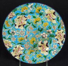 LONGWY POTTERY PLATE. Longwy enamel decorated pottery plate, with overall floral design on blue ground. Marked: Longwy.
