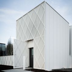 A diamond-patterned steel framework covered in a white mesh fence provides shading to the street frontage of this Belgian office building by CAAN Architects