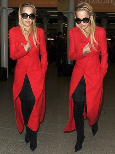 """Rita Ora wearing a red Atelier Versace coat, Versace """"Pop Medusa"""" sunglasses, black jeans, and black suede thigh-high boots"""