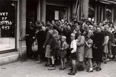 Bevrijding 1945. Eindelijk weer voedsel op de bon!. Direct na de bevrijding -en ook reeds ervoor, door de food-droppings- worden er weer bonnen voor voedsel aangewezen. Een genot voor de winkelier dat hij weer een vetbon op zijn winkelruit kan aankondigen, maar nog groter genot voor de bevolking, dat zij weer vet kunnen kopen, Amsterdam, Nederland 1945.