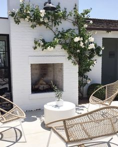 outdoor fireplace with white painted bricks. love the boho accents of this casual patio space, especially the woven wicker chairs!