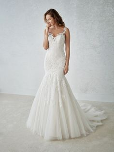 Lovely mermaid wedding dress with a low flared skirt in tulle. A sleeveless wedding dress that hugs the hips and the bodice, streamlining the silhouette. The illusion neckline and back in tulle with beaded embroidered appliqués create a marvelous second-skin effect.