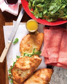 Inspired by calzones, these sandwiches are made by folding goat cheese, mozzarella, roasted tomatoes, and soppressata sausage into homemade pizza dough. Tuck a lightly dressed arugula and basil salad into the sandwiches just before serving.