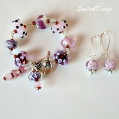 "One of a Kind handmade lamwork beaded bracelet and earrings set. The beads are a fun mixture of flowers, polka dots, and other lampwork designs in colors of ameithyst, pink, white, purple, lavender, and black. The set of pink bell beads attached to the clasp are Czech. Each bead was wire wrapped with high quality silver wire. A cute silver toggle clasp was added for closure. Bracelet measures approx 7"" end to end."