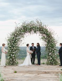 wild floral arch, except more asymmetrical and colorful florals. fuller on one side and tapers off. Will hide the bald spot on the  shrubbery behind the ceremony spot.