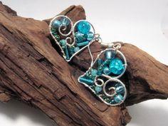 Srdcové náušnice - Nebe Srdcové náušničky jsou vyrobeny z odstínů modré a tyrkysové barvy. Materiál : měděný stříbrnýdrát, rokajl, broušené korálky, skleněné korálky Použité komponenty: bižuterní v barvě stříbra, afroháček, PVC puzeta Rozměry: délka: 2 cm šířka: 2,5 cm