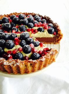 This isn't Claire Aldous' regular style of baking but it was certainly enjoyed by all at the office. A rich, avocado based chocolate mousse fills a chewy almond and date tart case and gets topped with a pistachio cream, fresh blueberries and juicy pomegranate seeds.